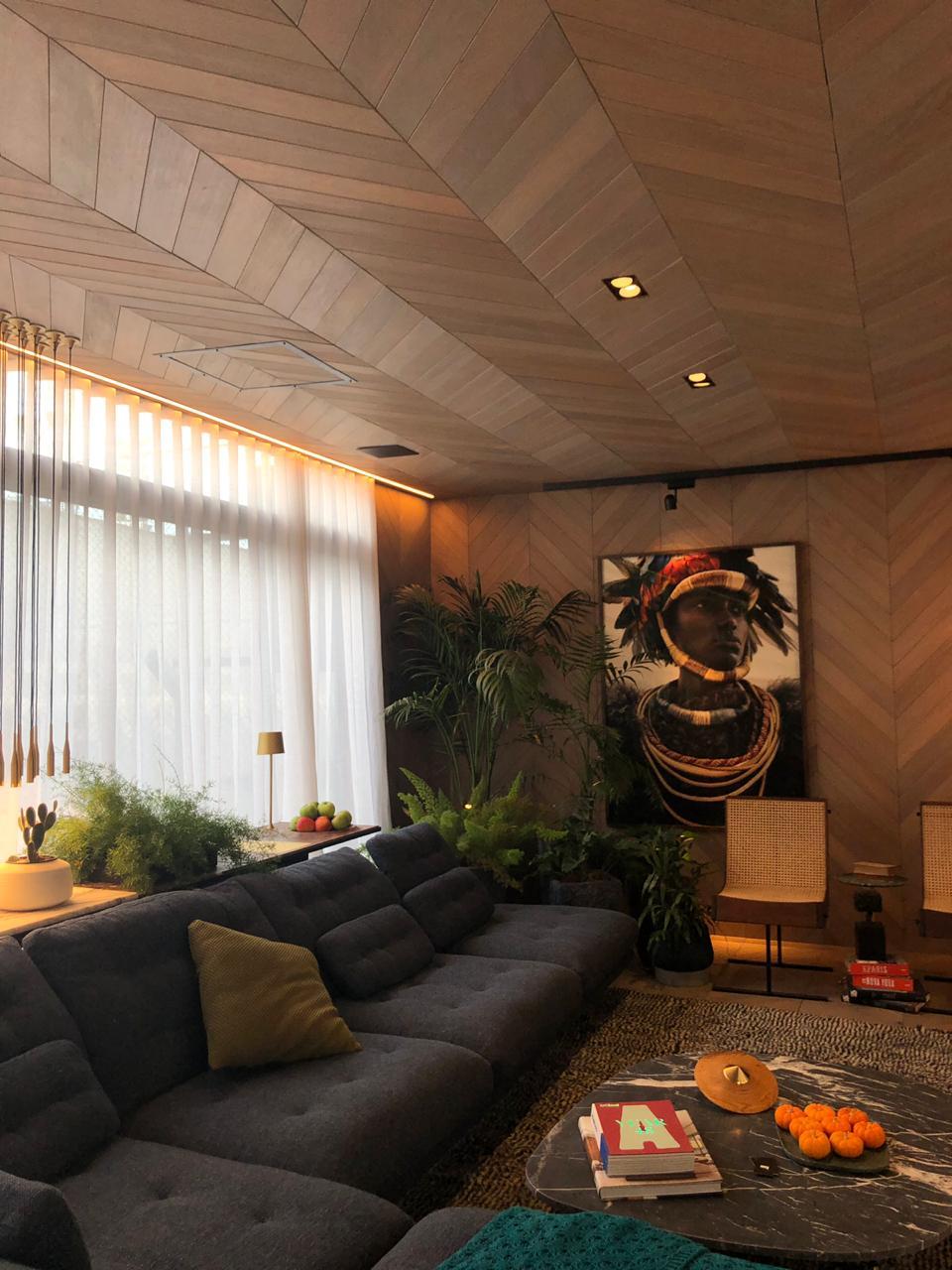 sala-com-sofá-cinca-e-parede-e-teto-de-madeira